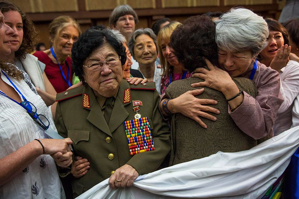 Women embrace at a quilt-stitching ceremony at the Women's Peace Symposium in Pyongyang. Photo by David Guttenfelder,