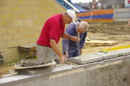 Ray & Reg putting coping stones on the new wall. These were specially made to fit.