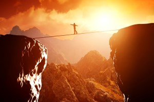 Person walking on tightrope over canyon