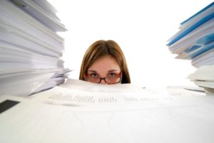 young business woman drowning in paperwork
