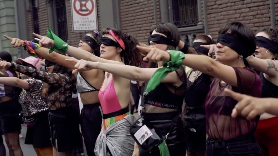 Women standing in a line pointing their fingers forward wearing black blindfolds.