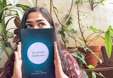 Tanvi with her copy of Small Wild Epiphanies
