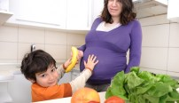 Pregnant woman with her boy in kitchen