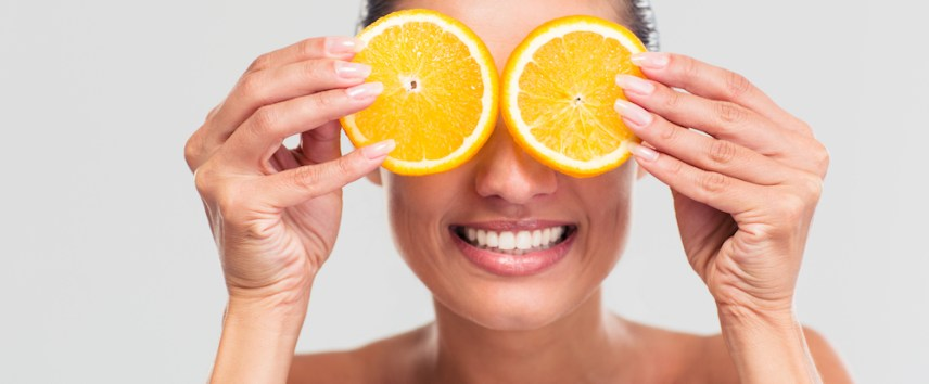 Beauty portrait of a smiling woman covering her eyes with orange isolated on a white background