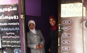 Sameera, Microfund for Women clients, stands smiling with her daughter outside their photo studio