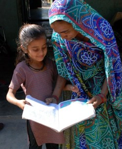 A SEWA Bank client and her daughter look over some financial education materials