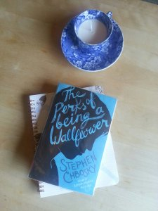 Paperback book the perks of being a wallflower by stephen Chboksy on top of a notebook with a teacup candle at the top