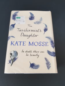 Hardback book the Taxidermist's daughter by Kate Mosse on grey background