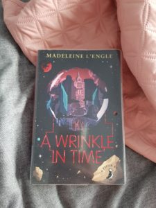 paperback book A wrinkle in time by madeleine L'engle on grey duvet with pink bedspread
