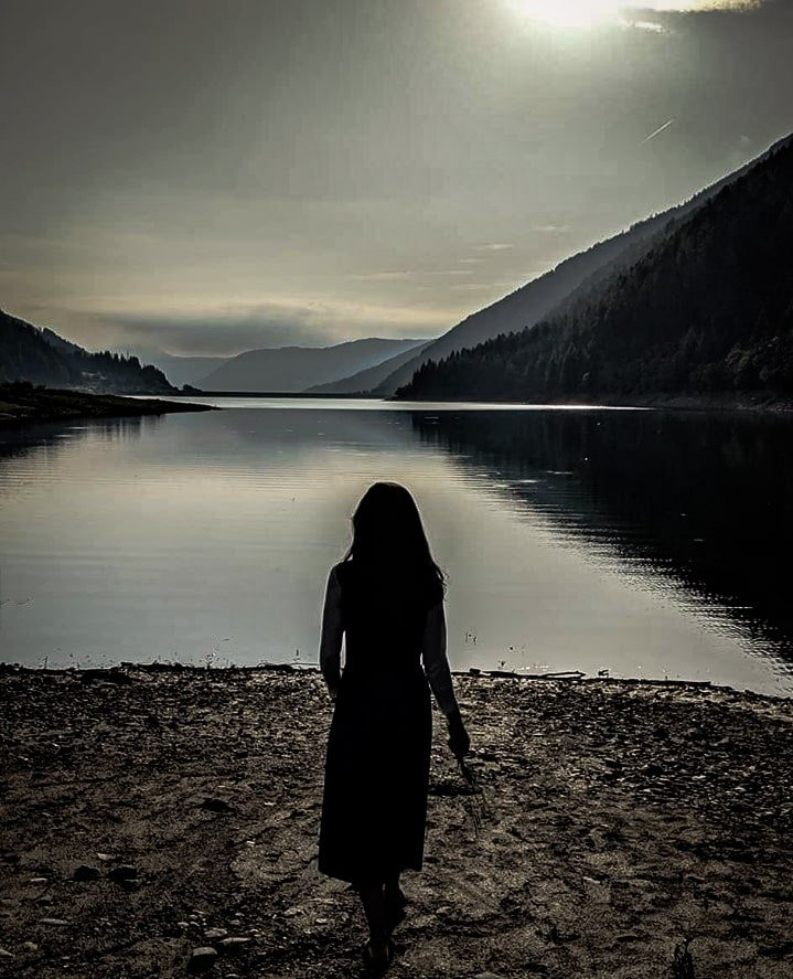 Woman in front of lake at sunset