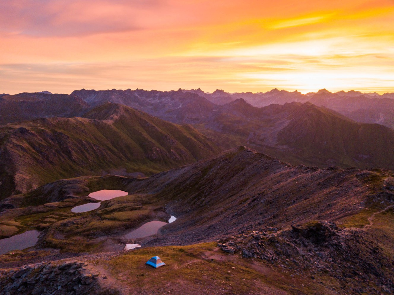 An aerial view of a single small blue tent as the sun rises in a spectacular burst of colors over a horizon of endless mountain peaks. The tent is well positioning on a mountain top above a few of alpine lakes.