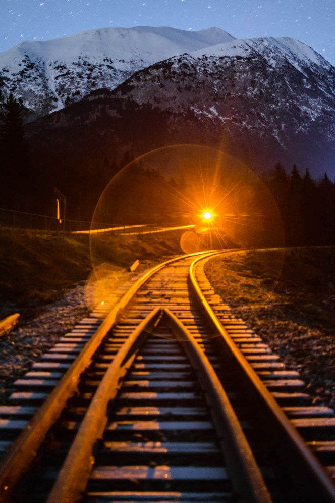 An amber warning light and lens flare are seen over the Alaska railroad at night among a backdrop of snow capped mountains.
