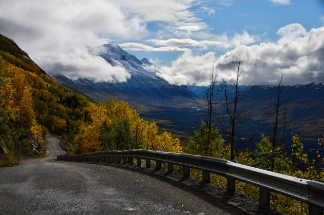 A winding road cuts down an autumn mountain in Eagle River Alaska. A guardrail protects the road from a steep drop. Spectacular views are seen of low clouds and a beautiful mountain valley.
