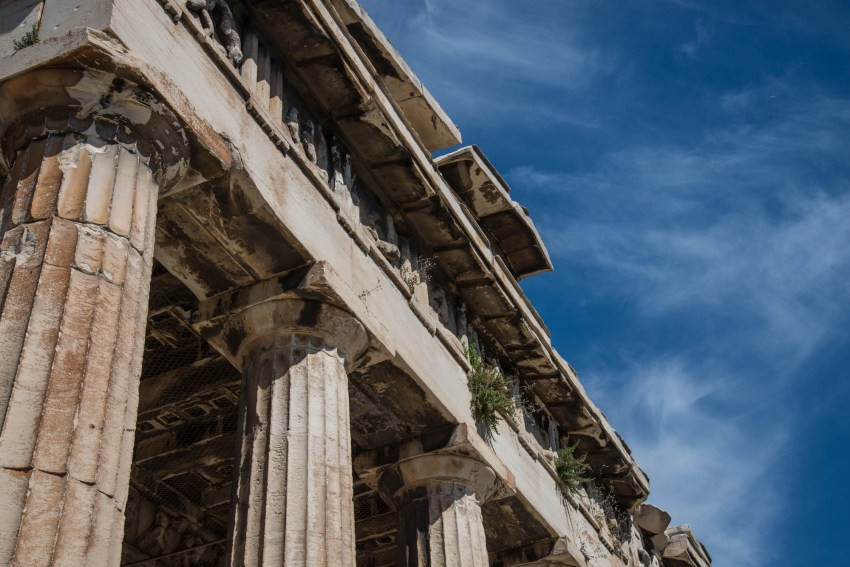 A close up of the Ancient Parthenon's marble columns and weathered roof against a backdrop of blue skys and light clouds.