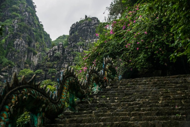 A colorful dragon statue decends a stone staircase on the hike to the Hang Mua Overlook Near Tam Coc Vietnam.