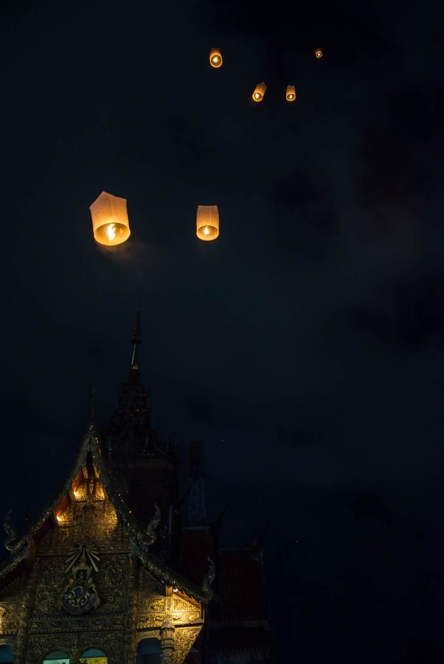 A few lanterns float up to the night sky above a golden buddhist temple in Chiang Mai Thailand. During the annual lantern festival.