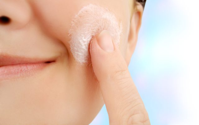 Woman gently exfoliating face