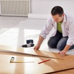 11891192 – home improvement – man laying new laminate flooring in empty room