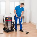 45165420 – happy male janitor vacuuming wooden floor in house
