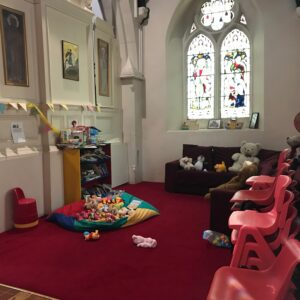 small carpeted area with seating, toy and books for children