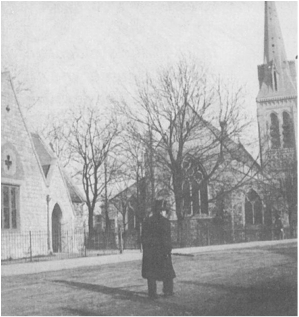 Man standing on green in front of church