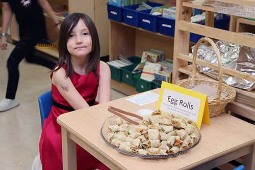 A student waits at a table to offer egg rolls to visitors