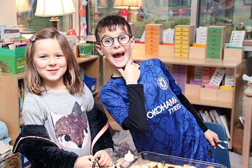 A girl and a boy pose for the camera.