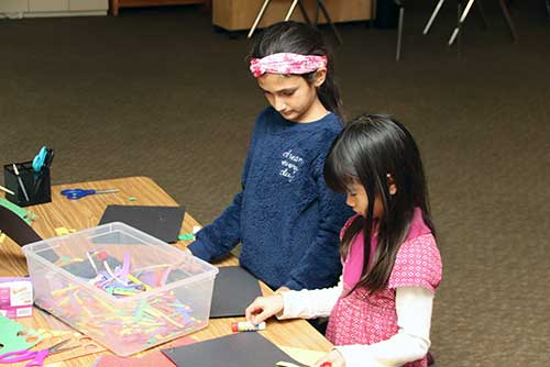A pair of Lower El girls works on a paper craft.