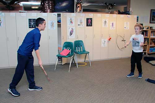 Two boys toss a hoop and catch it on sticks, demonstrating a Coast Salish game.