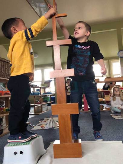 Two preschool boys work together to make a tall block tower. One boy stands on a stool.