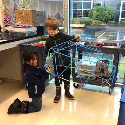 A boy and girl use building rods and connectors to make a dome shape
