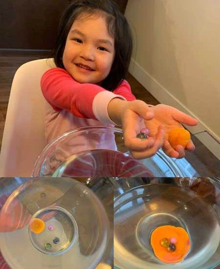 A girl holds out her hands showing items she has placed in a bowl of water
