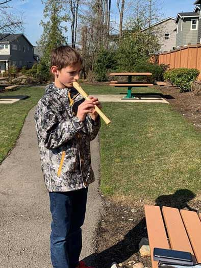 A boy plays a recorder outside