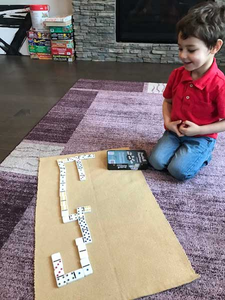 A boy sits in front a rug, with dominos laid out.