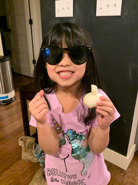 A girl smiles at the camera holding items that represent the letter G-glasses, garlic and glitter.