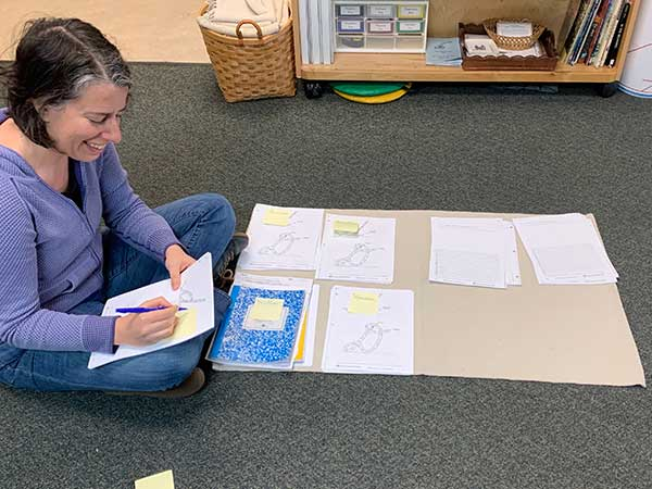 A teacher sits on the floor writing on sheaf of printouts