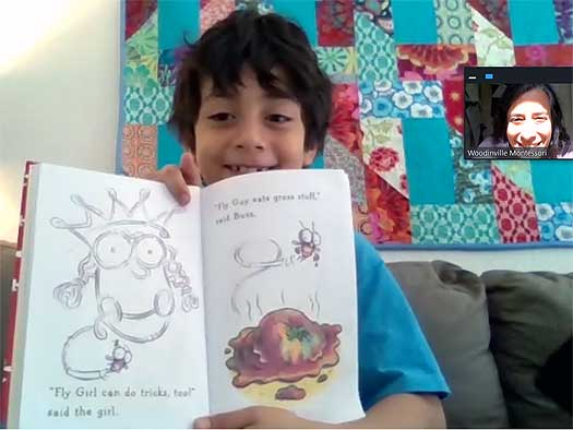 A lower elementary student holds up an open book for his teacher, who appears in an inset.