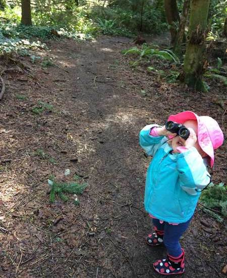 A toddler looks through binoculars during a walk in the woods.