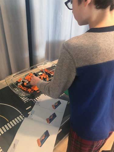 A boy reaches into a tray of orange and black Legos, with a visual manual open in front of him