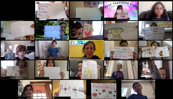 A videoconference screen capture of students and teachers holding up signs of appreciation