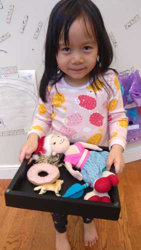"""A girl holds a tray of """"D"""" items-donut, dog, doll, dart"""