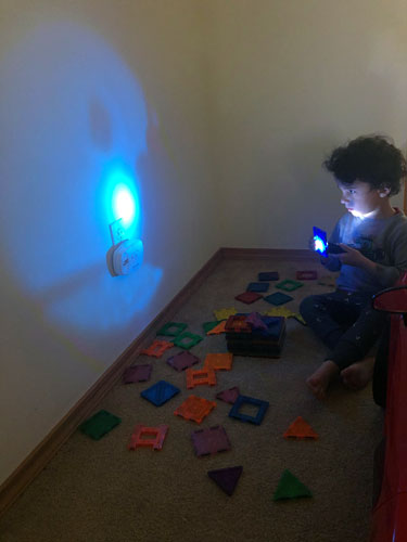 A toddler reflects blue light on the wall with a blue filter