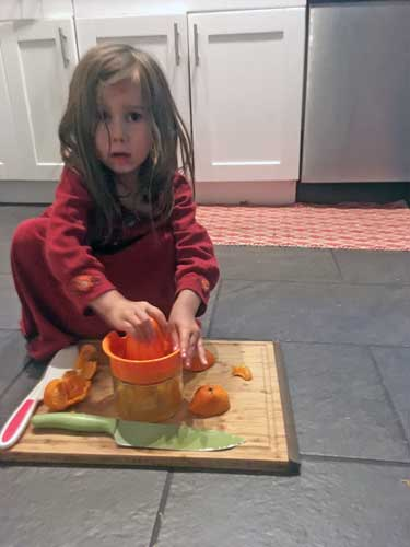 A preschool girl crouches on the floor, cutting pieces of orange for squeezing onto a wooden cutting board.