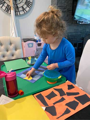 A toddler arrange irregularly torn pieces of various colors of construction paper