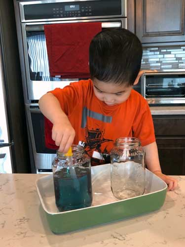 A toddler dips a strip of orange construction paper into a jar of blue-colored water