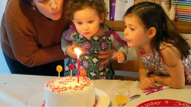 A mother holds up her toddler so that she and her sister can blow out birthday candles