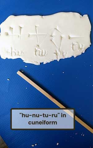 A piece of clay with impressions of symbols and an implement