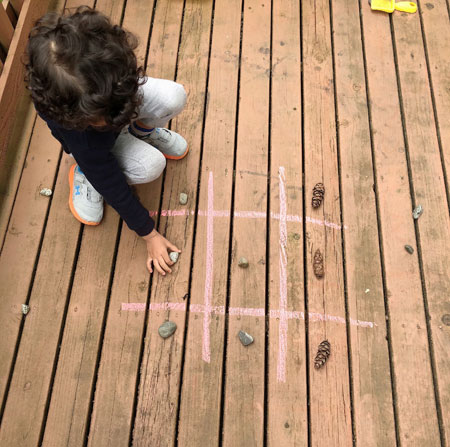 Tic tac toe with fir cones and rocks on the wooden deck