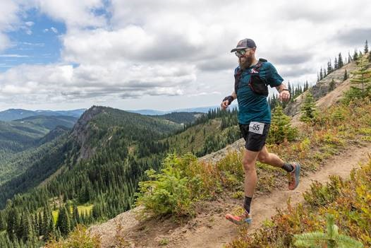 A bearded man in running gear runs on a mountain ridge trail