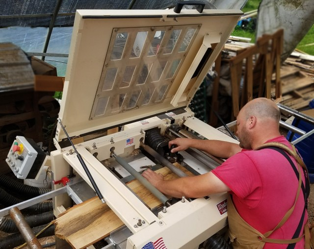 Jim Medeiros reaches under the hood to make adjustments to his 4-Head Woodmaster 4000.
